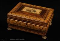 704JB: Ingeniously shaped box in rosewood and sycamore, decorated in penwork, inlay and a hand-colored print of idealised classical figures. It stands on the original gilded feet and has original handles. It is influenced by the second phase of the neoclassical tradition, when the early austere forms gave way to more monumental and even organic designs. An iconic gem of the period. inside it is lined with its original silk and has a replacement velvet covered tray. Circa 1815.