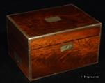"746JB:Box veneered in well figured mahogany with brass edgings and flat-folding handles. It has an unusual interior arrangement and a side drawer. Inside the lid there is an ""envelope"" Circa 1850"